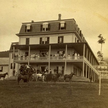 Guests are seen on the porches of the Alpine House in this photograph. Built in 1877 by Charles H. Clark, the stables burned in 1913. Courtesy of the Bethlehem Heritage Society.
